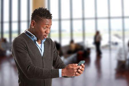 jonge Afrikaanse man verrast met zijn mobiele telefoon Stockfoto