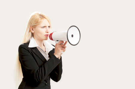 ironic: Businesswoman shouting into a megaphone isolated on white
