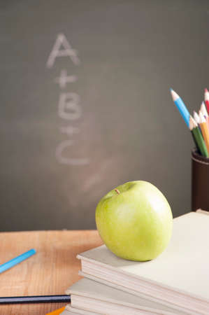 academia: A school teachers desk with stack of exercise books colored pencils and green apple. A green blackboard Stock Photo