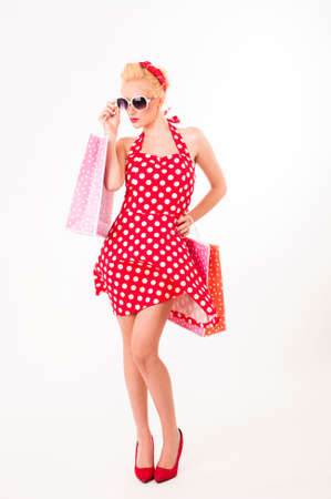 Portrait of beautiful young happy smiling woman dressed in pin-up style red dress in polka dot and holding shopping bag, isolated over white background.