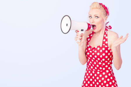 Portrait of woman holding megaphone, dressed in pin-up style red dress Stock Photo