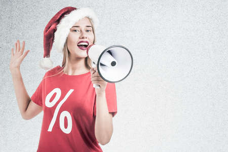 boxing day sale: Woman wearing a Santa Claus hat and wearing a red t shirt holding a megaphone Stock Photo