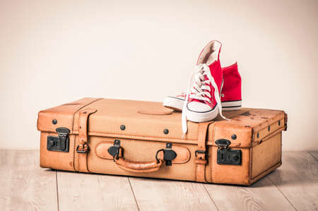 Sneakers on top of an old brown suitcase with a retro effect
