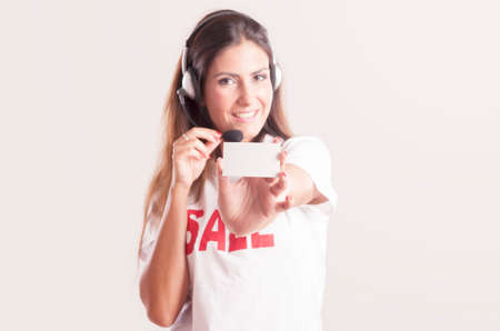 debet: Portrait of smiling cheerful customer support phone operator in headset, showing white blank business card