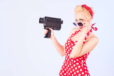 Pin-up girl holding vintage 8 mm camera