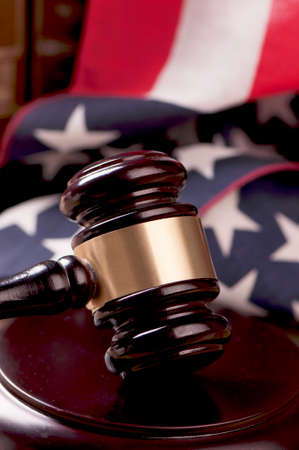 defendant: Judges wooden gavel with USA flag in the background Stock Photo