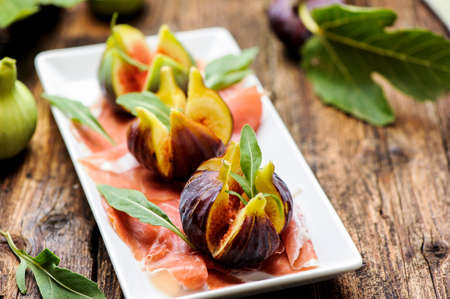 Parma Ham with figs on a wooden table