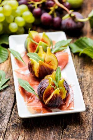 hams: Jamón de Parma con los higos en una mesa de madera