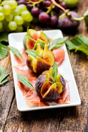 cold cut: Parma Ham with figs on a wooden table