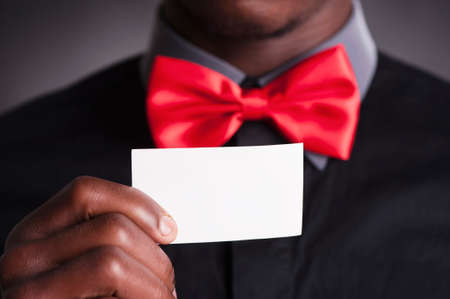 businness: Elegant man with red bow tie holding business card Stock Photo