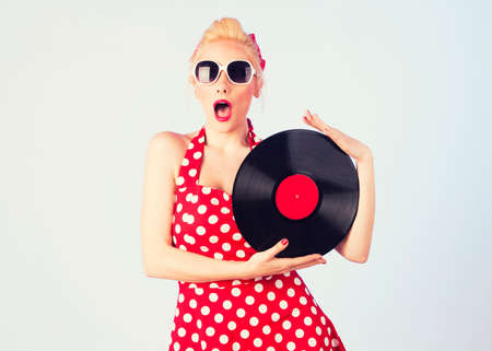 Pin-up girl in vintage jurk met een vinylplaat
