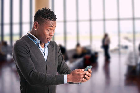 Portrait of surprised young african guy looking at cell phone