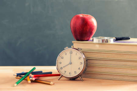 Some books and a pencil holder on a wooden table. Red apple is standing on the books. Stock Photo