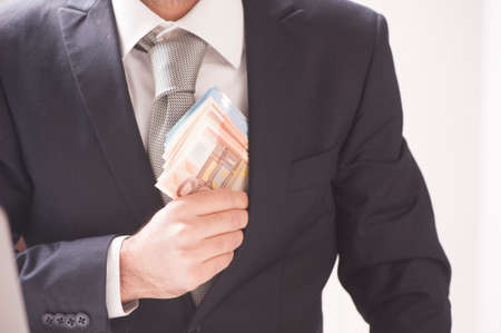 venal: A businessman in a black suit putting money in his pocket