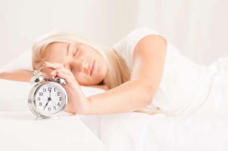 awaking: woman awaking up with alarm in bed at home