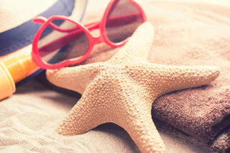 Starfish with glasses on a beach sand Stock Photo