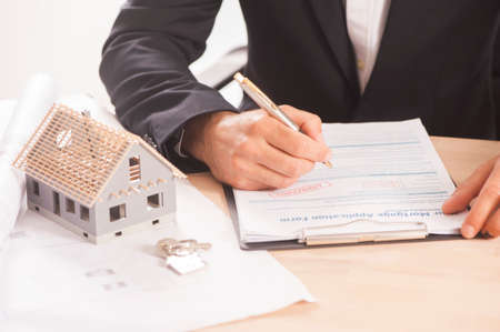 Businessman signing a mortgage  contract  of a sale for a new house Standard-Bild