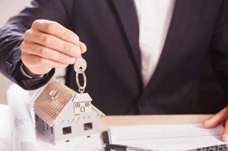 Real estate agent handing over house keys
