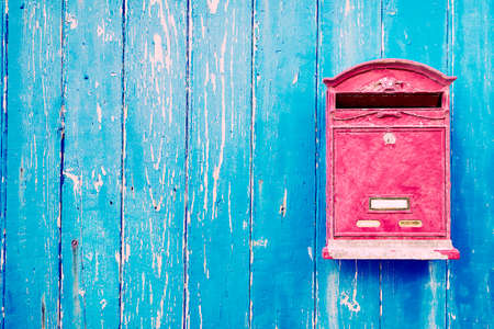 Red mailbox on blue wooden door