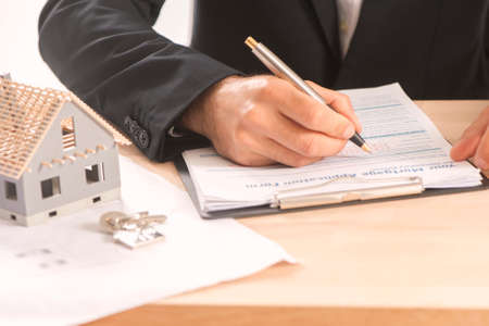 Businessman signing a mortgage  contract  of a sale for a new house Banque d'images