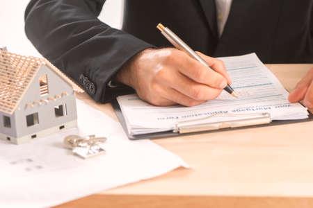 Zakenman die een hypotheekcontract van een verkoop voor een nieuw huis ondertekent