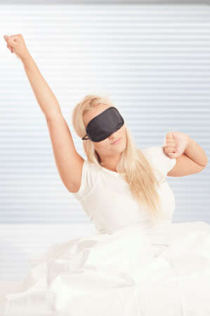 Blonde woman waking up in bed Stock Photo