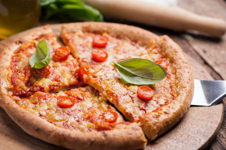 Italian pizza with tomato topped with melted golden cheese, herbs and basil served on a round wooden board on an old wood table