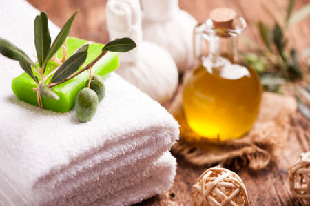 Olive oil soap and bath towel on wooden table Stock Photo