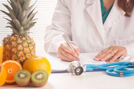 dietetics: Nutritionist writing medical records and prescriptions with fresh fruits