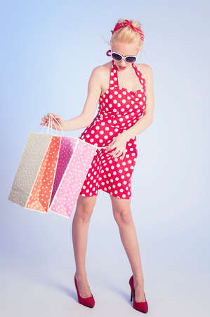 Retro pin up girl shopping. Woman holding paper bags