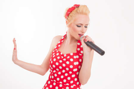 Portrait of a funny pin-up sing star talking into a microphone. Pop star karaoke