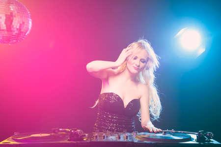 gogo girl: Schöne weibliche DJ mit Haufen von Vinyl-Schallplatten Lizenzfreie Bilder