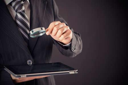 Het vergrootglas van de zakenmanholding en digitaal tabletconcept Stockfoto