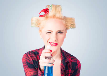 Housewife holding a cleaning spray in a pin up style Stock Photo