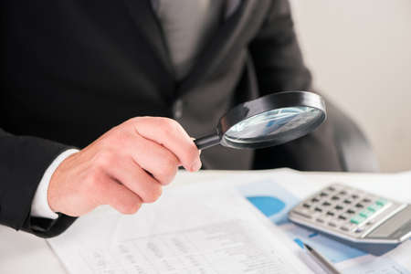 Businessman reading documents with magnifying glass concept for analyzing a finance