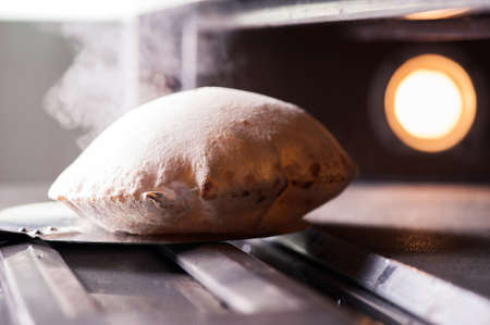 Italian calzone coming out from pizza oven