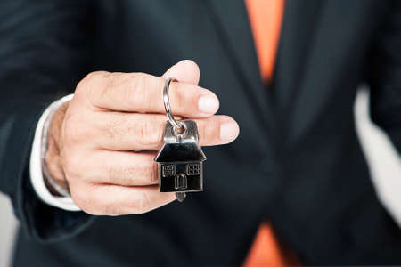 Real Estate Agent Handing over an house key. New concept House