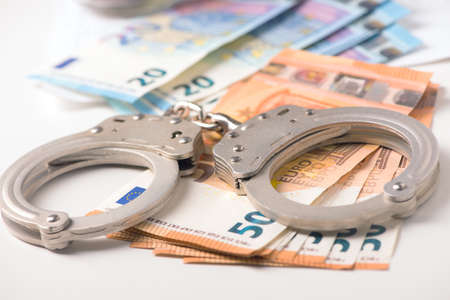 Handcuff and euro money. Crime fraud concept 스톡 콘텐츠