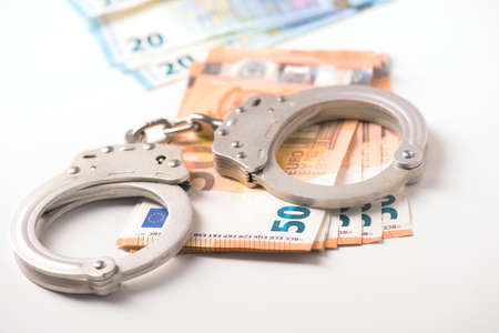 Handcuff and euro money. Crime fraud concept Stock Photo - 92261429