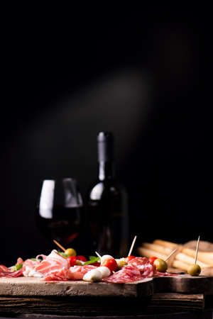 Assorted meats and  cherry mozzarella cheese, on a wooden cutting board with bottle of wine and glass on background. Italian antipasti Фото со стока