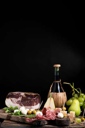 Flask of wine on a table with rustic traditional italian food.Fresh tipical italian lifestyle