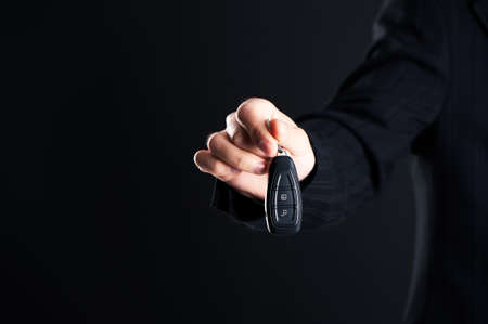Car salesman handing over your new car keys, dealership and sales concept on a dark background