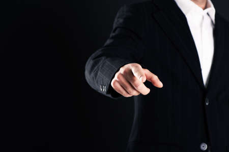 Business man pointing finger on dark background