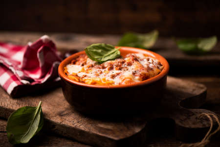 Traditional lasagne in a casserole dish on wooden table Imagens