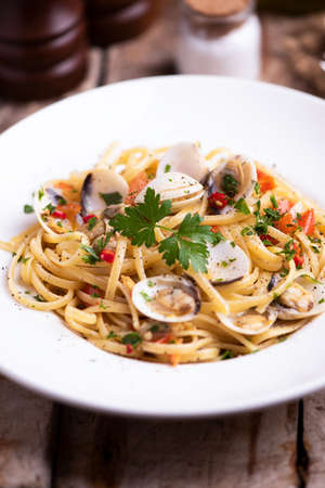 Linguine pasta in a clams sauce served on a white palte