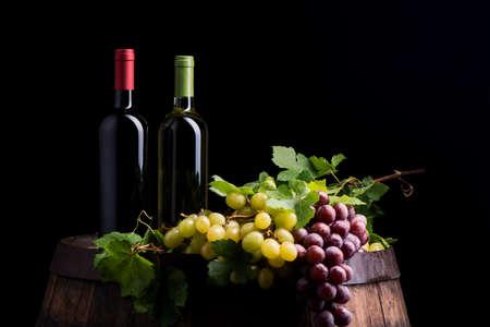 Two bottles of wine on dark background