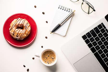 Doughnouts on a desk staion office. Break time concept Imagens