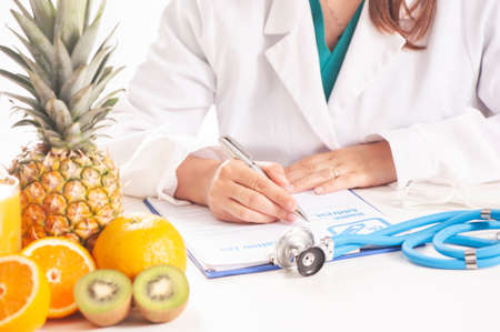 Nutritionist doctor writing diet plan on table.