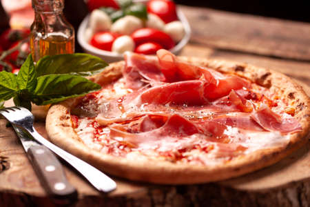 Pizza margherita with parma ham on a rustic table Stock Photo