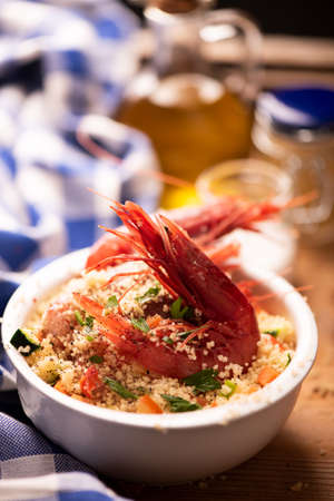 Fish and shrimps with couscous, garnished with fresh vegetables. Close up